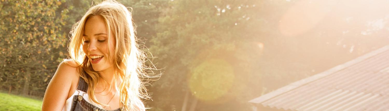 Lachende junge Frau im Garten bei Sonnenschein